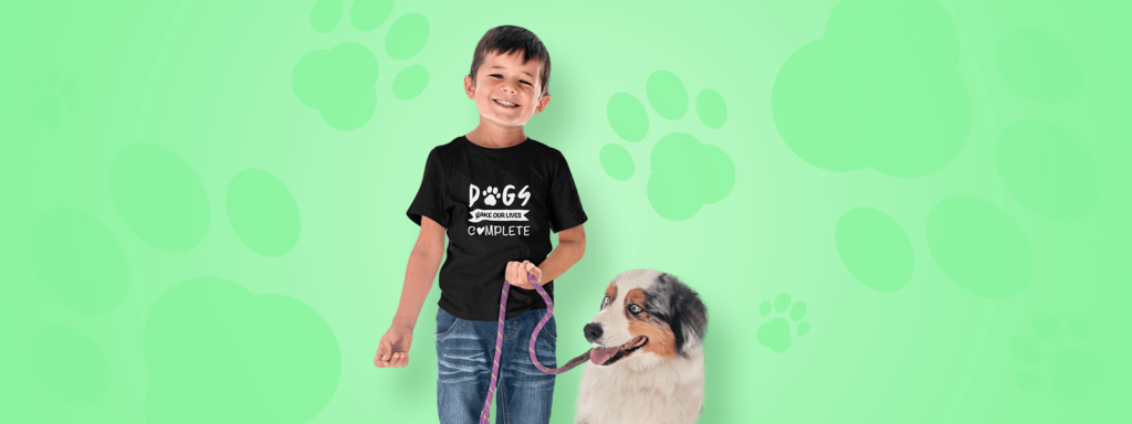 Boy wearing a dog design tee with a dog