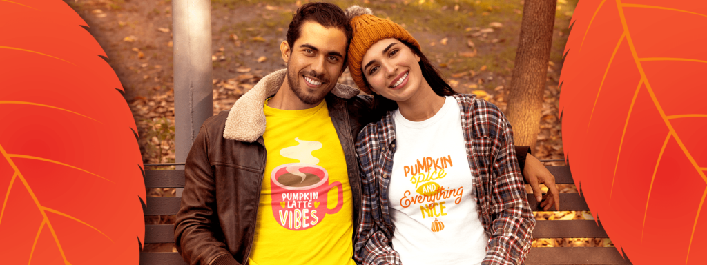 Couple wearing autumn design tees sitting on a park bench